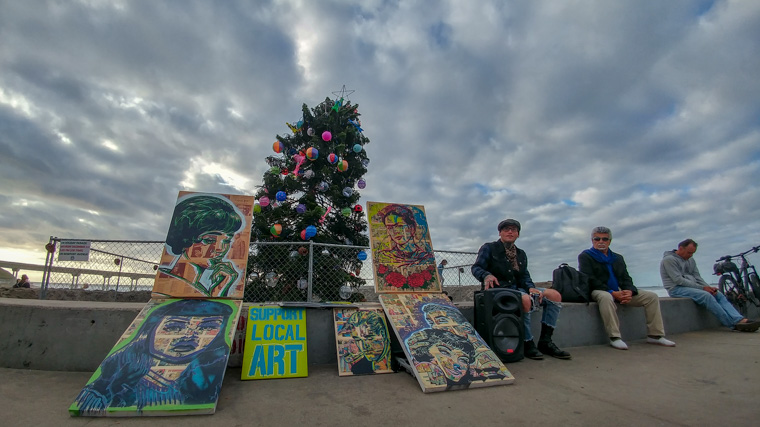 Art merchant in front of the Ocean Beach Christmas Tree (2018)