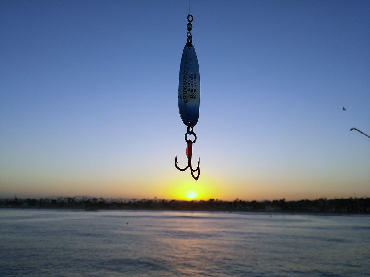 Lure hanging over the sun rise on the Ocean beach Fishing Pier
